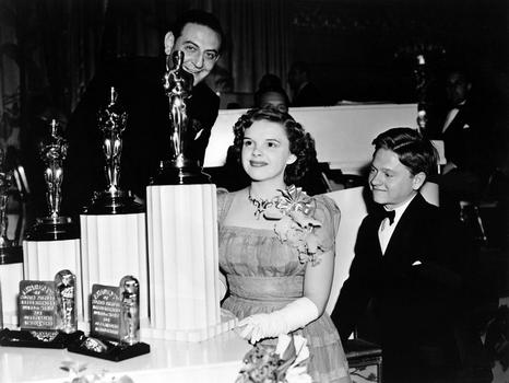 "Guy Lombardo, Judy Garland and Mickey Rooney, 1939 (12th) Academy Awards (Garland received a Special Award - a miniature statuette - ""for her outstanding performance as a screen juvenile"")"
