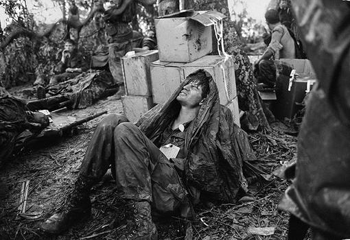 A U.S. paratrooper wounded in the battle for Hamburger Hill grimaces in pain as he awaits medical evacuation at base camp near the Laotian border, May 19, 1969.