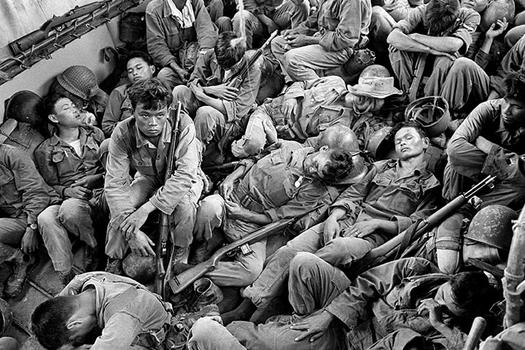 Exhausted South Vietnamese soldiers sleep on a U.S. Navy troop carrier taking them back to the provincial capital of Ca Mau, August 1962.