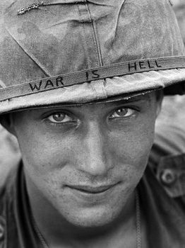 An unidentified American soldier wears a hand-lettered slogan on his helmet, June 1965. The soldier was serving with the 173rd Airborne Brigade on defense duty at the Phuoc Vinh airfield.