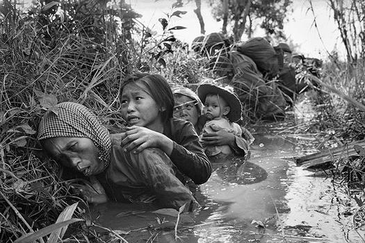 Women and children crouch in a muddy canal as they take cover from intense Viet Cong fire, January 1, 1966.