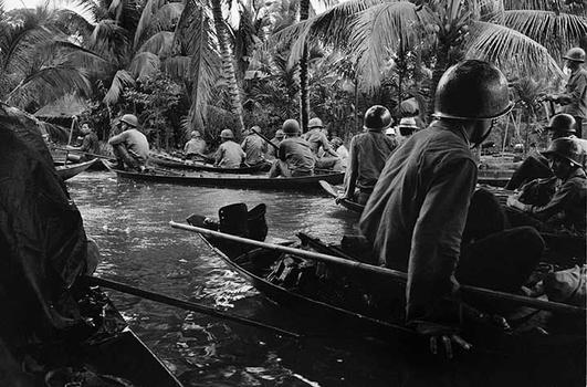 Caught in a sudden monsoon rain, part of a company of about 130 South Vietnamese soldiers moves downriver in sampans during a dawn attack on a Viet Cong camp, January 10, 1966.