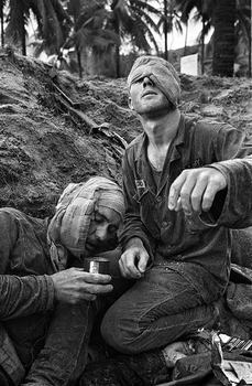 Medic Thomas Cole of Richmond, Virginia, looks up with his one unbandaged eye as he continues to treat wounded S.Sgt. Harrison Pell of Hazleton, Pennsylvania, during a firefight, January 30, 1966.