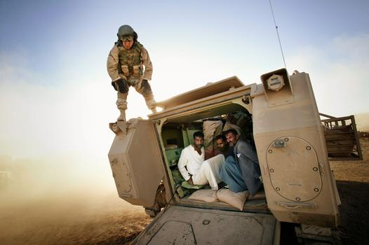 Tal Afar June 2005 - Suspected insurgents are detained inside a Bradley Fighting Vehicle to be transported to a detention facility during an early morning raid.