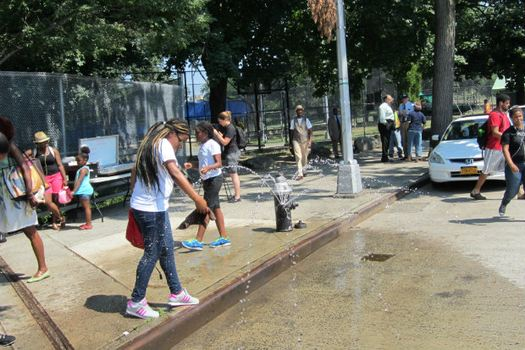Grand Concourse and 153rd Street, Bronx, DEP demonstrating hydrant with sprinkler cap.