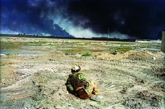Basra April 7, 2003 - A British soldier watches black smoke rising from the southern port city of Basra.