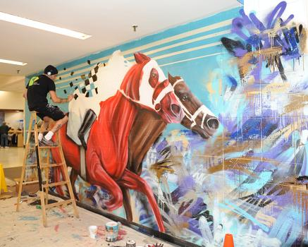 Artist Shai Duran working on a mural at Aqueduct Racetrack.