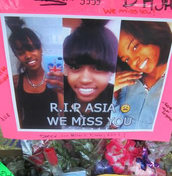 Images of the girl nicknamed 'Asia' hanging above flowers and other offerings at the memorial.
