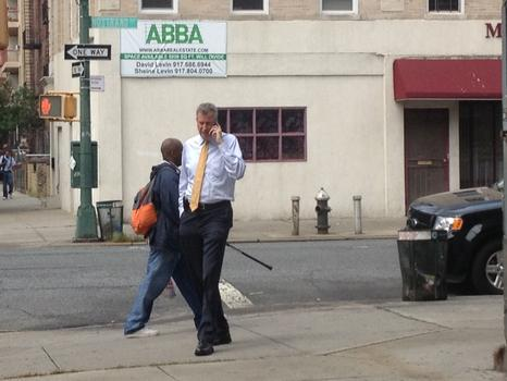 Before the first of two stops at Brooklyn senior centers, de Blasio paces alone on a street corner while taking a campaign-related phone call.