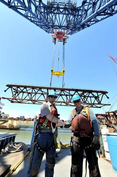 Two ironworkers on a barge, under the giant crane