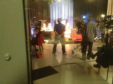 Lhota debating his Republican primary opponent George McDonald, as seen dimly through the glass door of a TV studio.