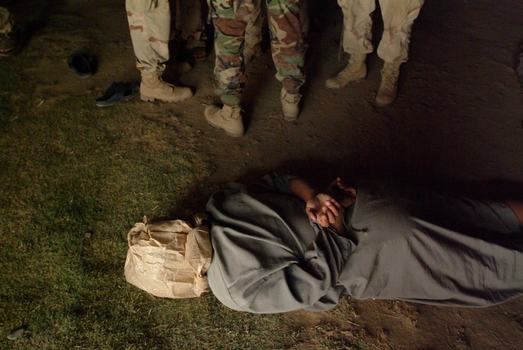 "Balad July 16, 2003- An Iraqi suspect in an early morning roadside attack on an American convoy is ""bagged and tied"" by American soldiers."