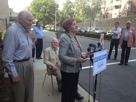 Christine Quinn lays out her plan for seniors outside a Bronx senior center with her father-in-law Anthony Catullo (left) and her father Larry Quinn (seated).