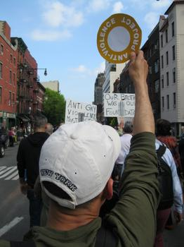 A marcher holds up a New York City Anti-Violence Project sign. The group tracks bias attacks and says there's been an increase in reports especially among transgender people in Brooklyn and Queens.