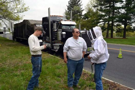 The truck driver (center) talks to two members of the New Jersey Beekeepers Association