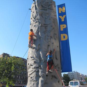 Kids were hoisted up a simulated rock climbing wall by uniformed officers.