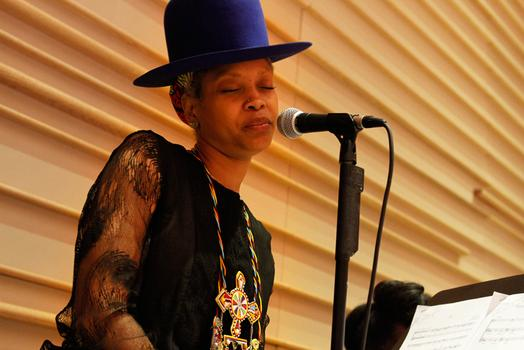 Erykah Badu closes her eyes during an instrumental passage of her song.