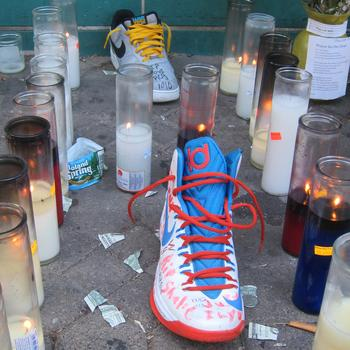 Shaaliver's sneakers and candles are part of a growing memorial to him outside his family's apartment in the Gouverneur Morris Houses.