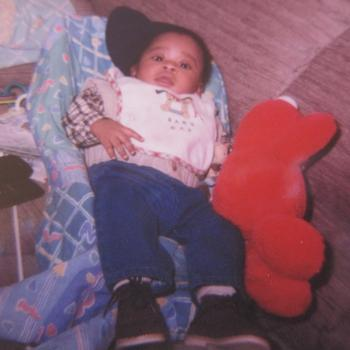 As a baby with Elmo, a favored toy.