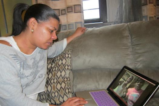 Arlene Delgado watches a video of  her son Raphael performing.