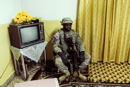 Rawah March 2006  - A weary American soldier stands guard as a residential home is searched.