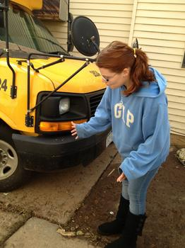 Tasina pointing out how high the water came up on her neighbor's school bus.