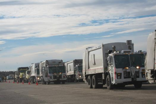 Lines of sanitation trucks wait to dump their hauls. The makeshift dump has been operating 24/7.