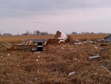 A field of wetlands on Mill Road appears to be covered in damaged homes.  But these are pieces of homes from the nearby streets that were blown or washed into the field.