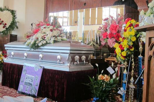 Ronald's prized basketball trophies next to his casket. His team uniform and flag were buried with him, according to the family.