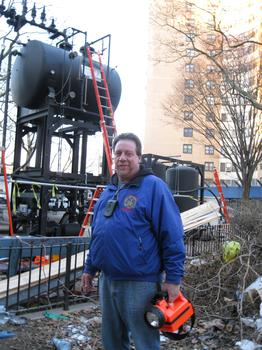 NYCHA Property Manager Phillip Calandrillo stands in front of a tank attached to a mobile boiler.