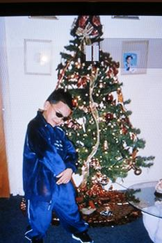 A school aged Jorge  posing near the Christmas tree with attitude