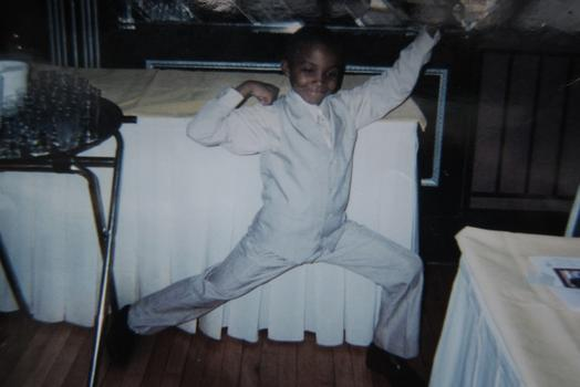 Kaiim is shown clowning around in a sharp white suit in family photos.