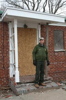 Superintendent David Luchsinger stands outside his now boarded up house on Liberty Island.