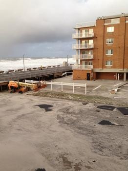 This view shows the damage outside of a condo building in Long Beach, NY. The building's pool is covered with sand.