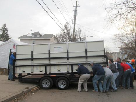 Volunteers and residents worked together to lift the trailer carrying the solar generator over the curb and into the yard.