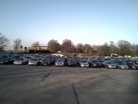 A vast parking lot by Belmont Park is a transit point for damaged cars