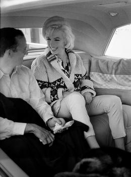 "Marilyn Monroe with Wally Cox, her costar in ""Something's Got to Give,"" driving to have dinner at Marlon Brando's home,  wearing a sweater she purchased from Saks Fifth Avenue."