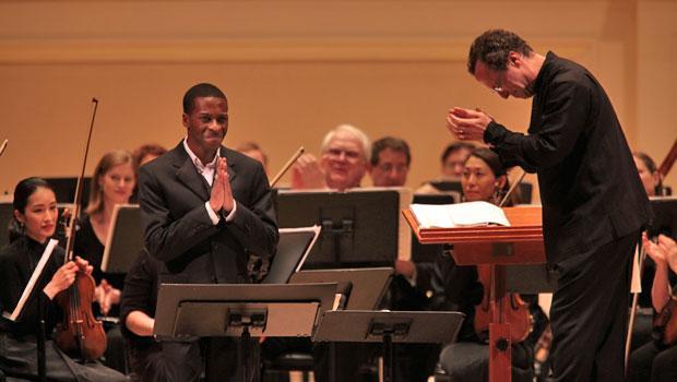 Conductor David Allan Miller bows to baritone soloist Nathan De'Shon Myers.
