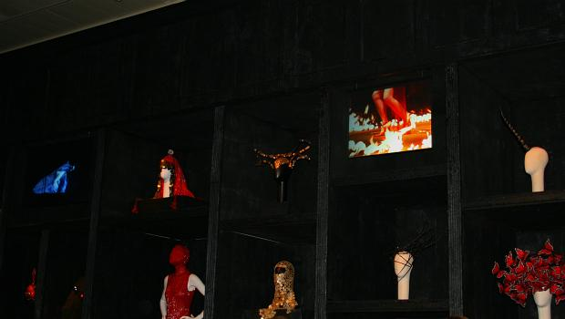 One of the show's rooms is a cabinet of curiosities, featuring fetishized accesories. Playing are eerie videos of runway models and robotic tape loops.
