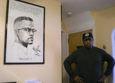Chuck D, at home with a poster of Malcolm X.