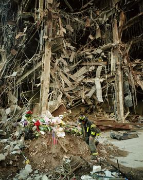 Image from <em>Aftermath,</em> Fireman places flowers on the debris.