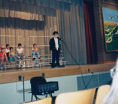 "6-year-old Eric singing ""Luck Be a Lady"" at his elementary school talent show"