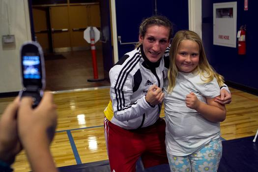 "Julia Irman won the German National Championship three weeks after giving birth to her son. Here she poses with a young fan. ""In a couple years I want to have another child. A girl. A boxer like me."""