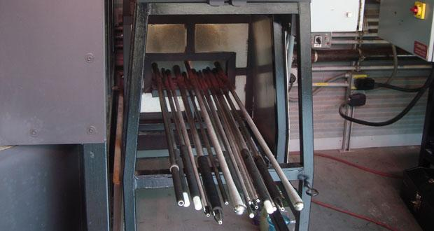 Glassblowing rods sit in an oven.