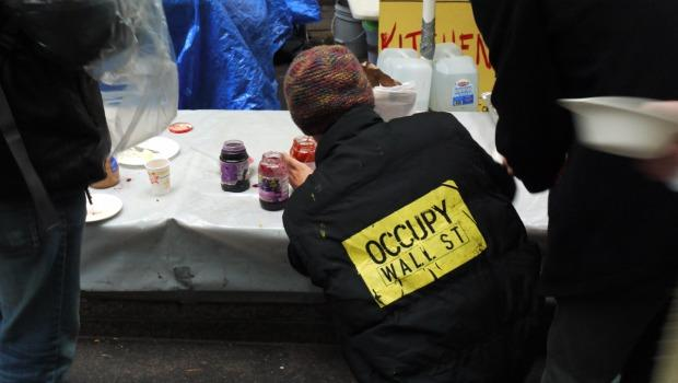 a concrete bench in the park is now the kitchen counter for donated food a protester helps himself to jam and bread