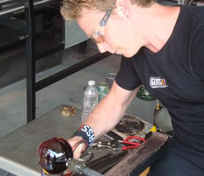 A glassmaker uses a metal tool to shape the glass.