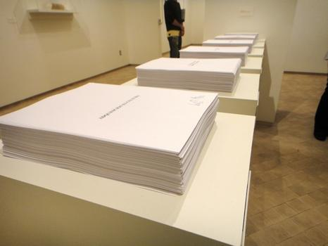 'Selbstbedienug (Self-Service/Autoservicio),' a piece by Camnitzer from 1996, in which museum viewers are invited to take sheets of paper printed with aphorisms in Spanish.