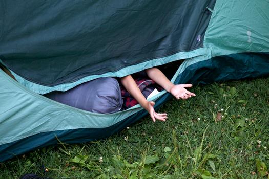 Campers fill their tents, while avoiding mosquitoes from flying into the tent.
