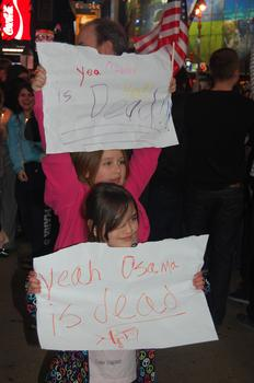As an apparently proud mother looked on, two girls held up signs celebrating the death of Osama Bin Laden.
