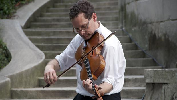 Orpheus Chamber Orchestra violist Daniel Panner warms up next to the Naumburg Bandshell in Central Park. Orpheus opened the 107th season of the Naumburg Orchestral Concerts on June 19, 2012.